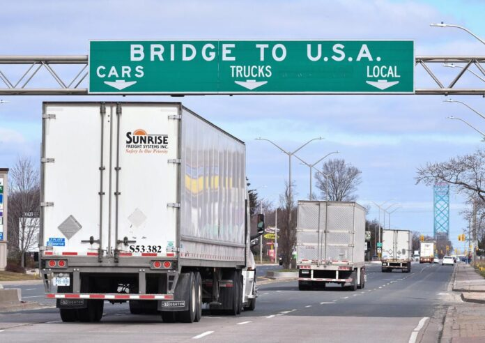 Transport trucks approach the Canada/U.S. border crossing in Windsor on March 21. A long-haul trucker in Woodstock has lost his job and will spend a month in jail after pleading guilty to sneaking a man into Canada this summer.