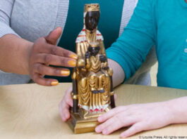 teacher and student with Our Lady of Montserrat statue - Warling Studios. (c) Loyola Press. All rights reserved.